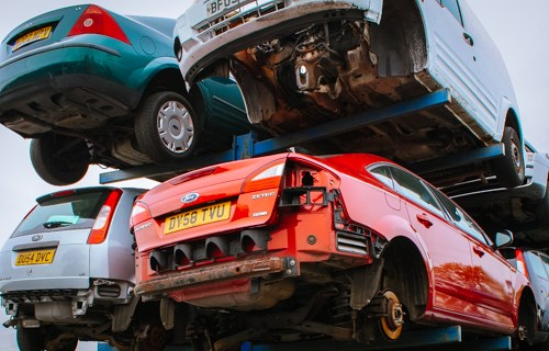 Fords in a scrap yard, being recycled for scrappage.