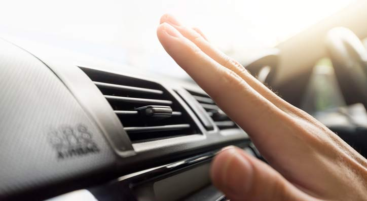 Hand checking air conditioning inside a car