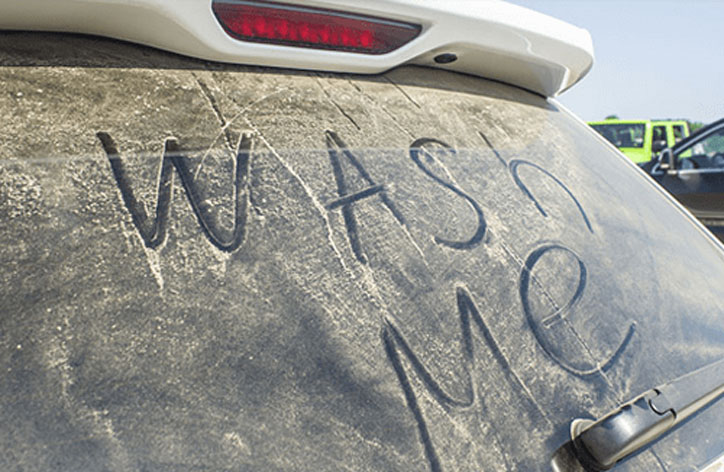Photo of dirty car with 'wash me' written on the screen